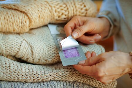 Closeup on modern woman in white sweater and skirt sitting near couch with pile of sweaters and using cloth anti moth lavender wardrobe repellent in the modern house in sunny winter day. Standard-Bild