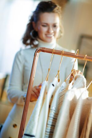 Closeup on smiling elegant 40 years old housewife in white sweater and skirt at modern home in sunny winter day choosing sweaters hanging on copper clothes rack.