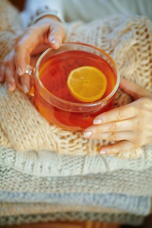 Closeup on elegant female in white sweater and skirt with pile of sweaters and cup of tea with lemon in the modern house in sunny winter day.