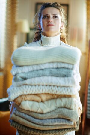 tired modern 40 years old woman in white sweater and skirt at modern home in sunny winter day holding huge pile of sweaters.
