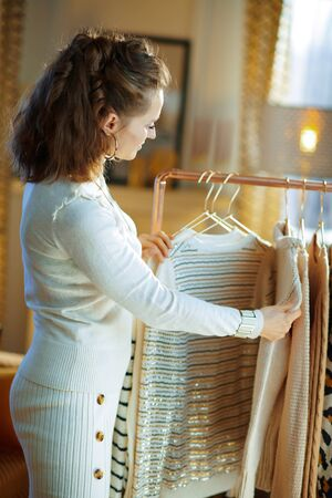 Seen from behind middle age woman in white sweater and skirt in the modern living room in sunny winter day choosing sweaters hanging on copper clothes rack.