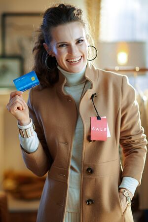 smiling young woman in white sweater and skirt trying beige coat with red sale price tag and holding blue credit card in modern fashion store. Banque d'images