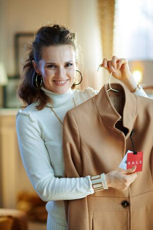 Portrait of happy stylish middle age woman in white sweater and skirt holding beige coat with sale price tag in modern fashion boutique. Banque d'images