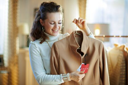 smiling elegant female in white sweater and skirt holding beige coat with sale price tag in modern fashion shop.