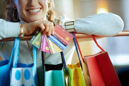 Closeup on smiling stylish woman in white sweater and skirt near colorful shopping bags hanging on copper clothes rail with a fan of credit cards.