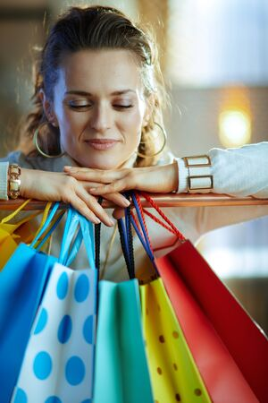 Portrait of relaxed 40 years old woman in white sweater and skirt near colorful shopping bags hanging on copper clothes rail.