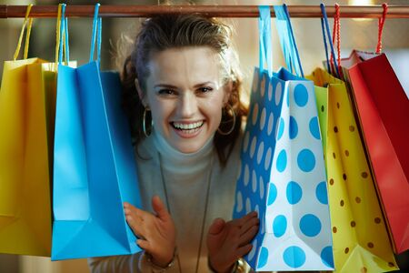 happy stylish woman in white sweater and skirt peeking out from colorful shopping bags hanging on copper clothes rail.