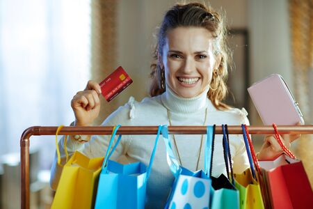 happy modern woman in white sweater and skirt near colorful shopping bags hanging on copper clothes rail taking out credit card from wallet. Stock Photo