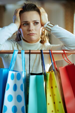 unhappy trendy middle age woman in white sweater and skirt near colorful shopping bags hanging on copper clothes rail.