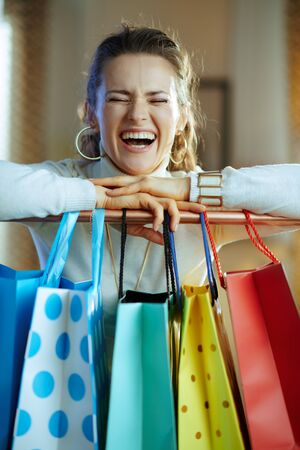 cheerful elegant middle age woman in white sweater and skirt near colorful shopping bags hanging on copper clothes rail.