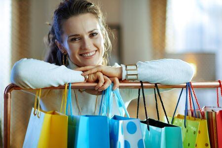 smiling modern woman in white sweater and skirt near colorful shopping bags hanging on copper clothes rail.