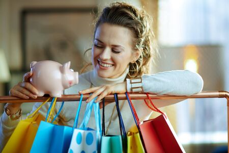smiling elegant middle age woman in white sweater and skirt near colorful shopping bags hanging on copper clothes rail with piggy bank.
