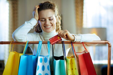 smiling stylish female in white sweater and skirt with credit card near colorful shopping bags hanging on copper clothes rail.