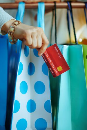 Closeup on young woman in white sweater and skirt with credit card near colorful shopping bags hanging on copper clothes rail.