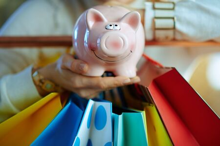 Closeup on trendy woman in white sweater and skirt near colorful shopping bags hanging on copper clothes rail showing piggy bank. Banque d'images