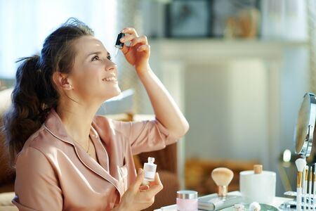 happy modern middle age woman in pajamas using cosmetic elixir near table with toiletries in the modern house in sunny winter day. Banque d'images