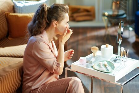 stylish housewife in pajamas applying facial cream and looking in mirror near table with toiletries in the modern house in sunny winter day.