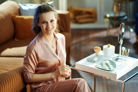 smiling modern housewife in pajamas with white facial cream heart on cheek holding cosmetic jar at modern home in sunny winter day. Stock fotó
