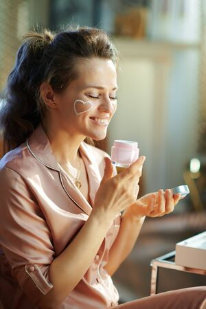 happy elegant housewife in pajamas with white facial cream heart on cheek smelling fragrance from open cosmetic jar in the modern living room in sunny winter day.