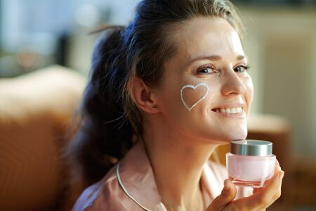 Portrait of happy young woman in pajamas with white facial cream heart on cheek holding pink cosmetic jar at modern home in sunny winter day.