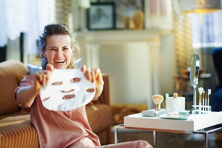 happy modern 40 years old housewife in pajamas with no makeup showing white sheet facial mask in the modern house in sunny winter day.