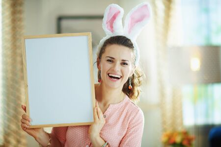 smiling modern woman in a pink blouse and easter bunny ears at modern home in sunny spring day showing blank white billboard. Фото со стока