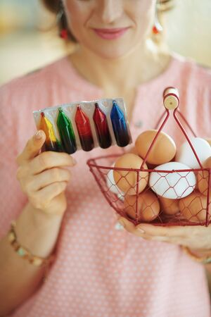 Closeup on female holding basket with eggs and reading instruction on food coloring pack in the living room in sunny spring day.