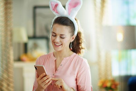 happy elegant housewife in a pink blouse and easter bunny ears with smartphone using app in the modern house in sunny spring day.