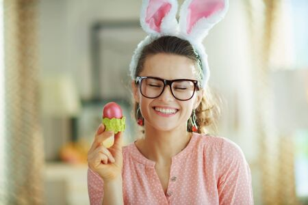 smiling modern housewife in a pink blouse and easter bunny ears with glasses holding red easter egg in green egg cup at modern home in sunny spring day.