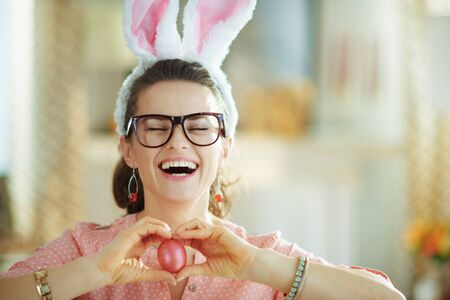 smiling modern 40 years old housewife in a pink blouse and easter bunny ears with glasses showing red easter egg in the modern living room in sunny spring day.