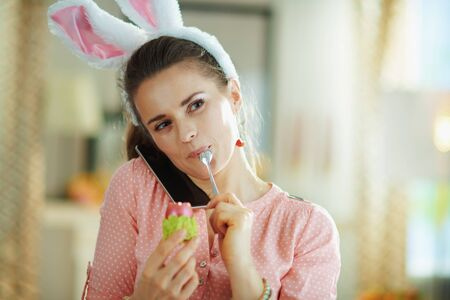 young 40 years old woman in a pink blouse and easter bunny ears speaking on a smartphone while eating red easter egg in green egg cup with spoon in the modern house in sunny spring day.