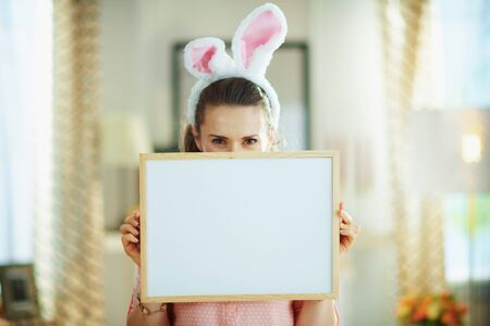 happy modern female in a pink blouse and easter bunny ears in the modern house in sunny spring day hiding behind blank white billboard. Фото со стока
