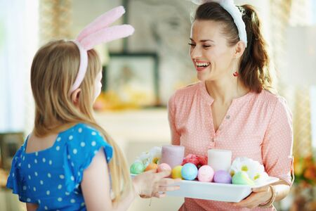 happy modern mother and daughter in easter bunny ears with easter decorated plate with colorful eggs and candles at modern home in sunny spring day. Фото со стока