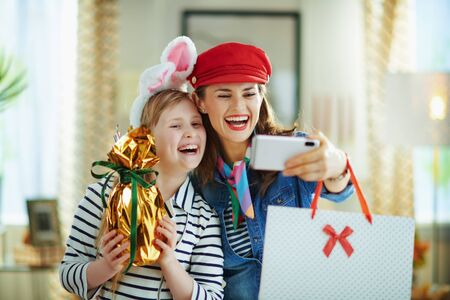 smiling stylish mother and daughter with wrapped in gold foil big easter egg and shopping bags taking selfie with phone in the modern living room in sunny spring day.