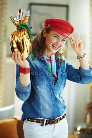 happy stylish middle age woman in a jeans shirt and red hat in the modern house in sunny spring day showing wrapped in gold foil big easter egg.