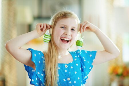 happy modern child in a polka dot blue overall and easter bunny ears making earrings with green decorative easter eggs in the modern house in sunny spring day.