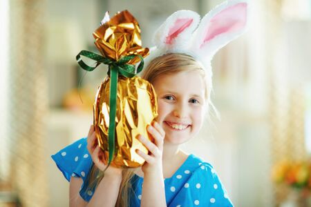 Portrait of happy modern little princess in a polka dot blue overall and easter bunny ears in the modern house in sunny spring day looking out from wrapped in gold foil big easter egg. 版權商用圖片