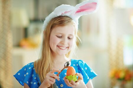 smiling modern child in a polka dot blue overall and easter bunny ears eating easter egg in green egg cup with spoon at modern home in sunny spring day.