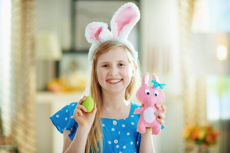 happy modern girl in a polka dot blue overall and easter bunny ears at modern home in sunny spring day showing pink rabbit toy and green easter egg.