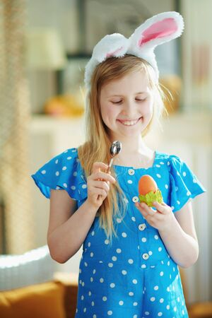 happy modern child in a polka dot blue overall and easter bunny ears eating easter egg in green egg cup with spoon at modern home in sunny spring day. 版權商用圖片