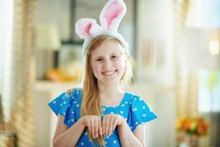 Portrait of smiling modern girl in a polka dot blue overall and easter bunny ears in the modern house in sunny spring day.