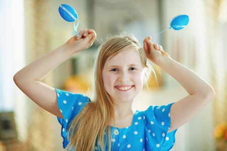 Portrait of cheerful modern child in a polka dot blue overall making ears with blue easter eggs in the modern house in sunny spring day.