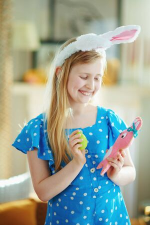 happy modern little princess in a polka dot blue overall and easter bunny ears playing with pink rabbit toy and green easter egg in the modern house in sunny spring day. Standard-Bild