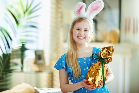 happy modern girl in a polka dot blue overall and easter bunny ears at modern home in sunny spring day holding wrapped in gold foil big easter egg.