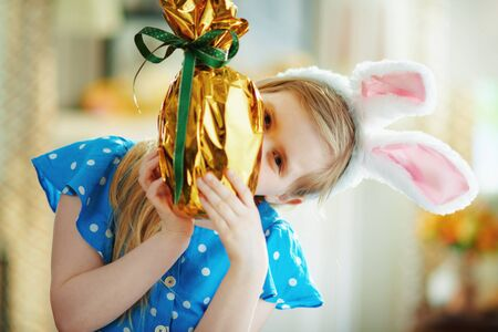 modern child in a polka dot blue overall and easter bunny ears in the modern living room in sunny spring day looking out from wrapped in gold foil big easter egg.