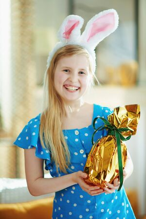 Portrait of smiling modern child in a polka dot blue overall and easter bunny ears at modern home in sunny spring day holding wrapped in gold foil big easter egg.