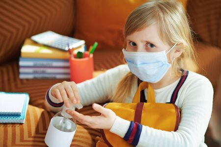 young girl in white striped t-shirt with medical mask and backpack sitting near divan and sanitizes hands with a disinfectant in the modern living room in sunny day.