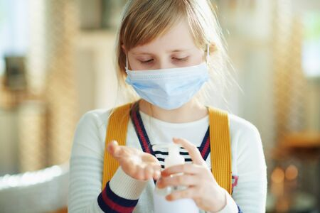 modern girl in white striped t-shirt with medical mask and backpack sanitizes hands with a disinfectant in the modern living room in sunny day.