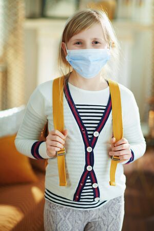 young child in white striped t-shirt with medical mask and backpack at modern home in sunny day.