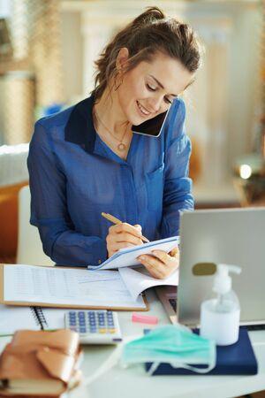 Stilvolle Frau mittleren Alters in blauer Bluse im modernen Zuhause an sonnigen Tagen, die während der Coronavirus-Epidemie auf einem Mobiltelefon telefoniert und im vorübergehenden Heimbüro arbeitet.